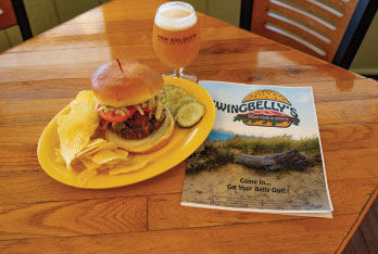 Swnigbelly's burger on table with beer in mug and menu laying closed.